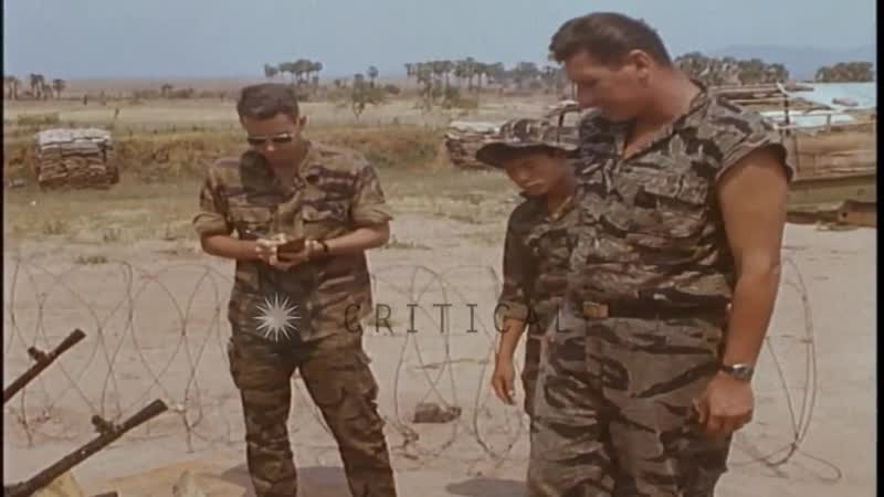 US officer observes captured ammunition while Army of Republic of Vietnam ARVN