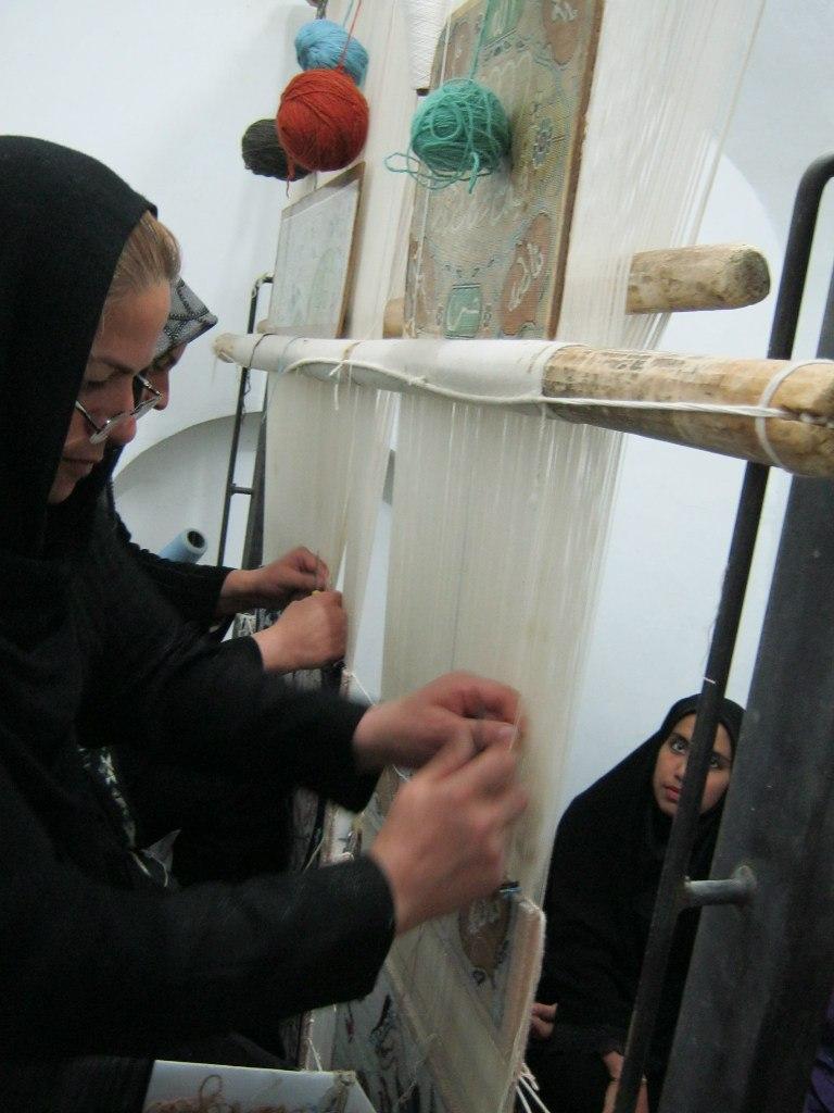традиционное ручное производство ковров на базаре в Иране