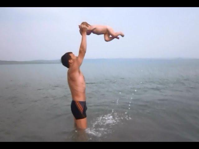 Купание ребенка в озере. Оздоровительные водные процедуры.