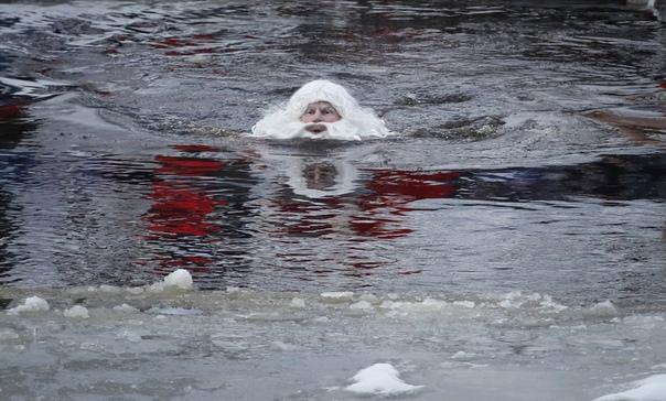 """Участник """"Олонецких игр Дедов Морозов"""" купается в ледяной реке Олонке."""