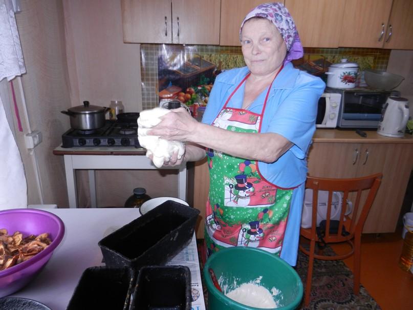 В.Ф.Кузьмина раскладывает тесто по хлебным формам.